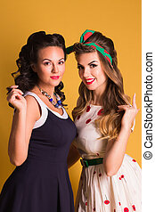 Two smiling women in dresses pose in orange studio, pin up style
