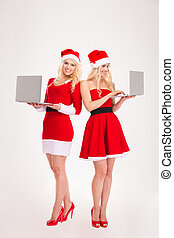 Two smiling women in santa cloth using laptop computer