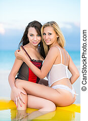 Two smiling women in sexy lingerie