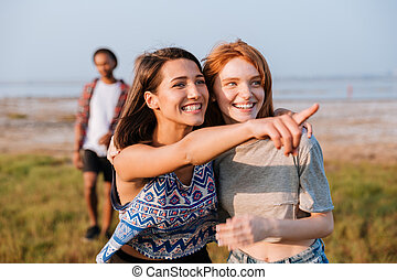 Two smiling women looking and pointing away outdoors