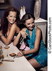 Two smiling women showing something