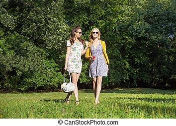 Two smiling women walking on the fresh meadow