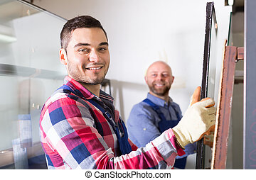 Two smiling workmen at factory - Two cheerful smiling ...
