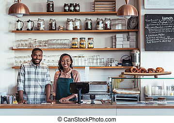 Two smiling young African entrepreneurs standing at their...