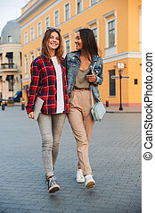 Two smiling young girls friends walking together
