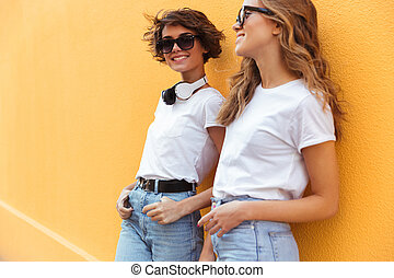 Two smiling young teenage girls posing outdoors