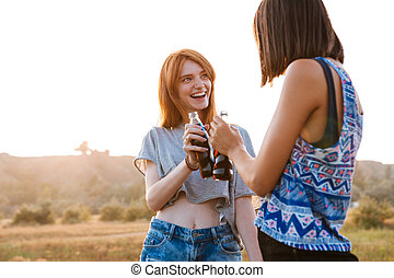 Two smiling young women drinking soda outdoors