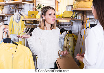 Two smiling young women friends talking in clothes showroom