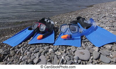 Two snorkeling sets on wild pebble beach