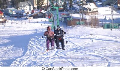 Two snowboarders riding up ski lift on sunny day. 3840x2160...