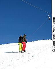 Two snowboarders on the t-bar ski lift