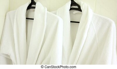 Two soft white bathrobes hang on hanger, downward motion