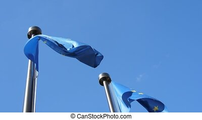 Two solemn EU banners fluttering on metallic flagpoles in...