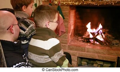 Two sons and father sitting near fireplace