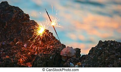 Two sparklers or bengal fire and spiral seashell on rocky coast colorful shot