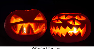 two spooky pumpkins on black background