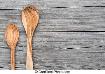 spoons of olive wood on grey table - two spoons of olive ...