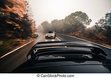Two sport sedan cars, metallic and black color on the road, driving with high speed.