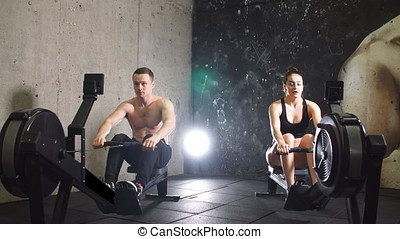 Two sportsmen sitting on rowing machines and working out in...
