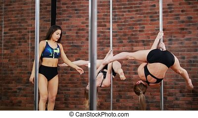 Two sporty women improves skills in a pole fitness class...