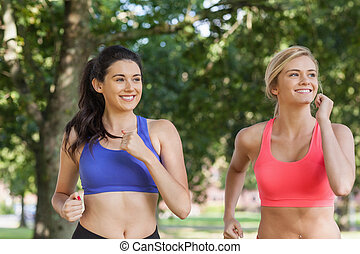 Two sporty women jogging in a park