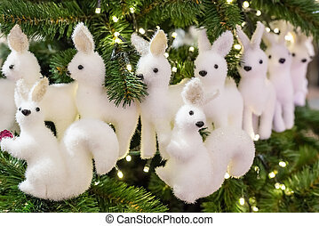 two squirrel toy christmas white on the background lots of deer and branches of furry fur-trees