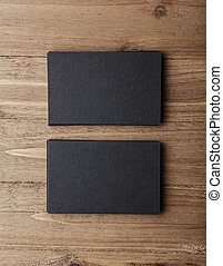 Two stack of blank black business cards on wooden background Vertical