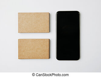 Two stack of craft business cards and smartphone on white background. Horizontal