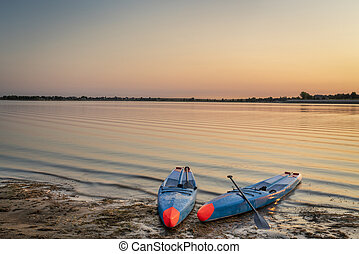 two stand up paddleboards on a shore before sunrise - Boyd Lake State Park in northern Colorado, a popular boating and recreation destination.