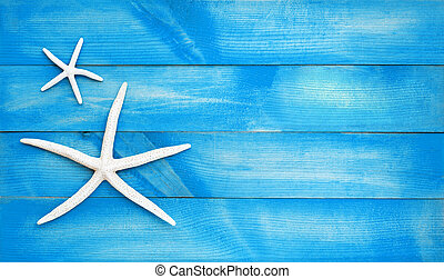 Two starfish on blue wooden background. Top view