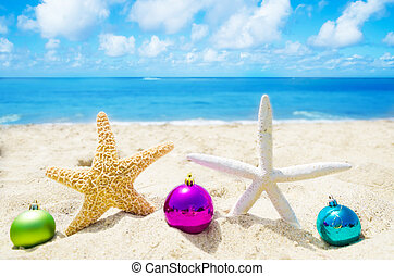 Two Starfishes with Christmas balls on sandy beach in sunny...