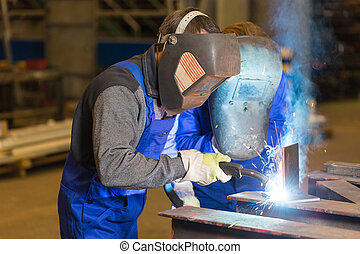 Two steel construction workers welding metal pieces