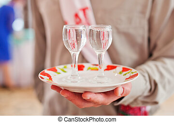 Two stemware of vodka on a plate - Two glasses of vodka on a...