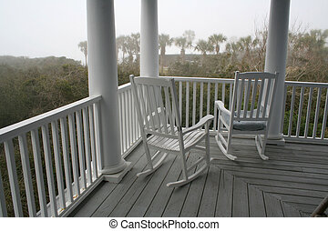two white painted rocking chairs on porch in a hazy morning...