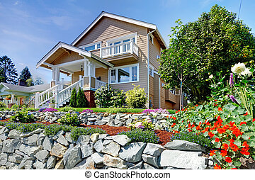 Two story beige nice house on the rocky hill with flowers.