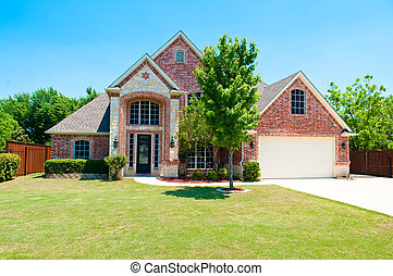 Two story brick home with the garage in the front.