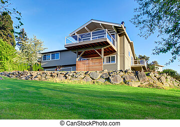 Two story house exterior with gray siding and natural stone landscape design.