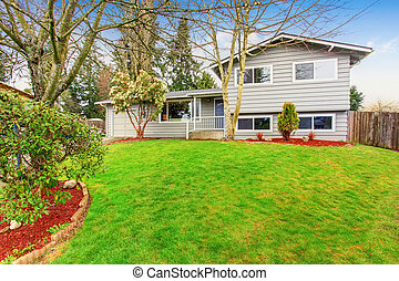 Two story house with garage, driveway and well kept lawn.
