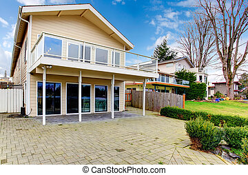 Two story paneled house with glass balcony and stoned porch,...