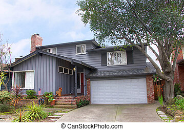 Two story ranch style house, gray wood siding with red brick work