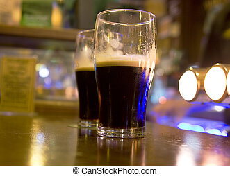 Two stouts on bar - Two half full stout beers on a bar