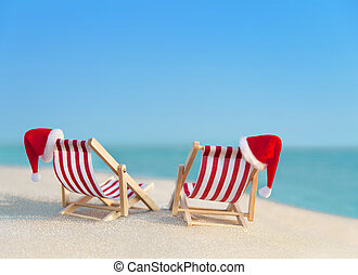 Two striped deckchairs with Christmas Santa hats at ocean...