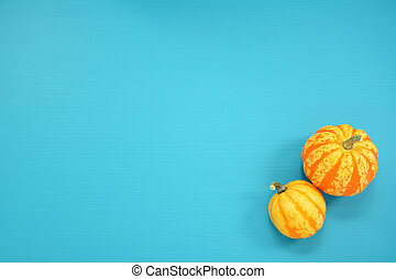 Two striped Festival squash on a teal background