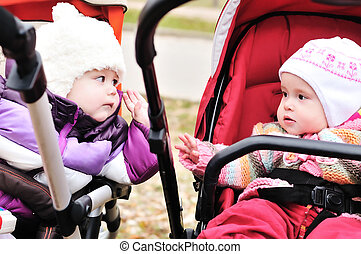 two strollers friends - two baby girls sitting in strollers...