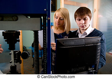 Two students in front of the monitor in the workshops