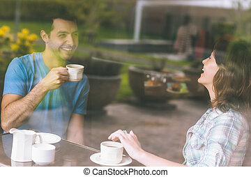 Two students laughing having a cup of coffee