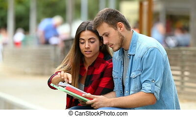 Two students learning together in a park - Two students...