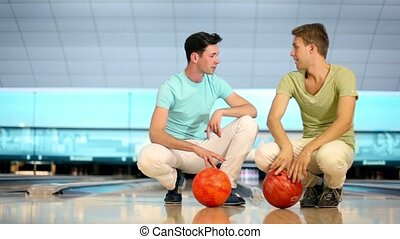 Two students sit and spin balls at background of bowling lane