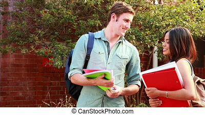 Two students standing and chatting on college campus