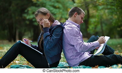 Two students studying in autumn park writes something in notebooks